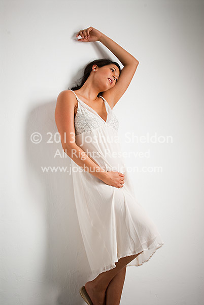 Pregnant Hispanic woman, arm over head, leaning against white wall