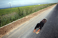 A Tibetan man prostrates near Qinghai Lake. The Lake is regarded as holy by locals and is revered as 'the soul of Qinghai'. Qinghai Lake is China's largest inland body of water, lying at over 3000m on the Qinghai-Tibetan Plateau. The lake has been shrinking in recent decades, as a result of increased water-usage for local agriculture. Qinghai Province. China. 2010