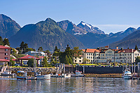 """View across the Sitka Harbor, from Japonski Island, overlooking the coastal fishing community of Sitka, on Baranof Island, southeast, Alaska. Commercial fishing vessel, """"Swift"""" passes through Sitka Channel."""