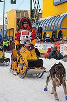 Musher Mitch Seavey and Iditarider Carol Stedman.leave the 2011 Iditarod ceremonial start line in downtown Anchorage, Alaska