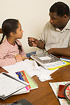 10 year old girl with father at table discussion about homework serious