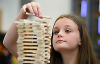 Sloan Cook, 11, of Yukon, Okla. uses Keva planks to build a structure, Friday, July 16, 2021 at the Amazeum in Bentonville. The Amazeum's latest exhibit Creativity Cubed: Think Outside the Blocks, created by the Amazeum team, invites guests to explore their own creativity through a timeless medium - the block. Blocks are infinitely adaptable to the imagination of the user. Check out nwaonline.com/210717Daily/ for today's photo gallery. <br /> (NWA Democrat-Gazette/Charlie Kaijo)
