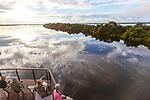Navigation sur le Rio Negro au nord de Manaus sur le bateau de croisière La Jangada<br /> Les nuages et le bateau se reflètent dans les eaux noires du Rio Negro