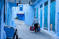 Chefchaouen, Morocco.  Man Carrying Bread and other Purchases from the Market.