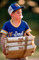 Boy in little league baseball uniform holding bases and blowing a bubble gum bubble.