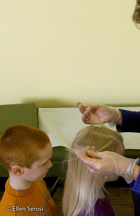 MR / Schenectady, NY.Yates Arts-in-Education Magnet School (urban elementary school).School nurse checks 2nd grade students (girl, boy, aged 7) for head lice in the nurse's office using disposable gloves..MR: AD-g2f Kli10 Ris2 Feu3..© Ellen B. Senisi
