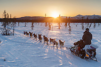 Noah Burmeister and team run down the trail near sunset after leaving the Kaltag checkpoint on Saturday March 12th during the 2016 Iditarod.  Alaska    <br /> <br /> Photo by Jeff Schultz (C) 2016  ALL RIGHTS RESERVED