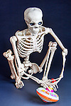 Skeleton plays with antique tin top toy.