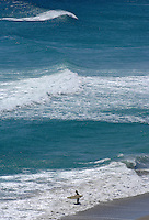A lone surfer heads out into the water as the waves roll in.