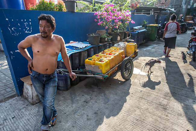 13 August 2019, Jakarta, Indonesia: Local water seller Mohammad Yusuf, delivers water in plastic barrels to homes in Muara Baru, North Jakarta. There is a severe lack of water facilities that the local poor population has access to. Water is hauled in each day by motorcycle and trucks and by hand to allow residents of the kampungs (village) to buy it for washing and to do laundry. Separate water is needed for drinking. The Jakarta Governor is proposing a program to send in trucks of water for the locals to get for free to ease their plight. They are living in villages below the seawater line on the coast of Jakarta that is sinking faster than anywhere else in the world.They have the position of being surrounded by water yet not having access to clean supplies. Picture by Graham Crouch/The Australian