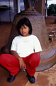 Missoes, Rio Grande do Sul State, Brazil. Black haired girl in white t-shirt and red trousers sitting on the bell of Sao Miguel. The bell weighs one ton and was cast locally in Sao Joao Batista, Missoes.