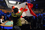 Tuan Lam, from Toronto, waves the Canadien flag after doubling up through Jerry Yang.