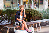 Attractive female shopper talks on a mobile smart phone at an Austin outdoor shopping mall