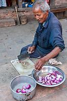 Bhaktapur, Nepal.  Man Cutting Onions.