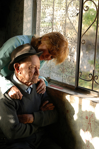 A woman caresses her aging father by a window with a lace curtain and heart in his home in rural Ecuador.