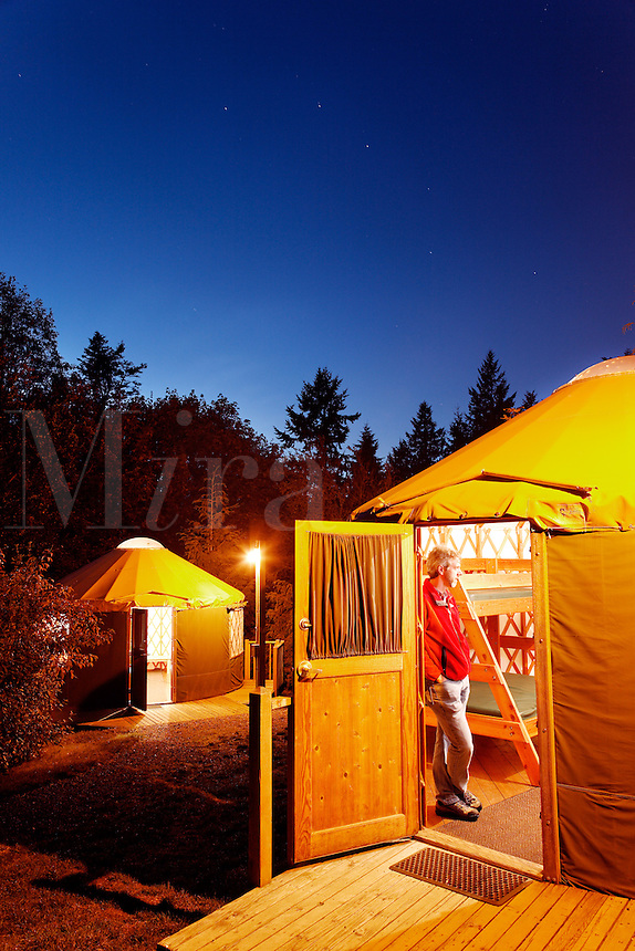Man standing in open doorway of rental yurts at Kayak Point County Park at dusk, Snohomish County, Washington, USA