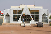 Senegal, Touba.  Man Entering CBAO, a Private Bank Headquartered in Dakar.  (Compagnie Bancaire de l'Afrique Occidentale).