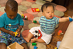 15 month old and 12 month old toddler baby boys sitting next to each other playing with toys horizontal