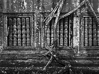 Beng Mealea was built as a Hindu temple, but some carvings depict Buddhist motifs.Its primary material is sandstone and it is largely unrestored, with trees and thick brush thriving amidst its towers and courtyards and many of its stones lying in great heaps. For years it was difficult to reach, but a road recently built to the temple complex of Koh Ker passes Beng Mealea and more visitors are coming to the site, as it is 77 km from Siem Reap by road.<br />