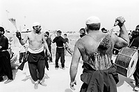 """Iraq. Basra. Al Fao neighbourhood. The procession and the celebration for the religious commemoration of the day of Ashura. During the ceremony, moslem men hit themselves in the back with chains-whipes and show their sadness. Body self-flagellation rituals. Blood on the back of a man. Muharram is a month of remembrance that is often considered synonymous with the event of Ashura. Ashura, which literally means the """"Tenth"""" in Arabic, refers to the tenth day of Muharram. It is well-known because of historical significance and mourning for the martyrdom of Hussein ibn Ali, the grandson of Muhammad. Shi'a Muslims start the mourning from the 1st night of Muharram and continue for two months and eight days. However the last days are the most important since these were the days where Hussein and his family and followers were killed in the Battle of Karbala which took place on Muharram 10, in the year 61 of the Islamic calendar (October 10, 680). Muharam's month is considerated as one of the most important feast for the Shiism branch of Islam. Shia Islam is the second largest denomination of Islam. The followers of Shia Islam are called Shi'ites or Shias. Basra ( in arabic Al Basrah) is the capital of Basra Governorate in southern Iraq. 02.03.04 © 2004 Didier Ruef"""