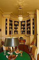 A curved built-in cabinet with glass doors in the oval games room displays three Vieux Paris dinner services