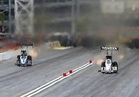 Mar 30, 2014; Las Vegas, NV, USA; NHRA top fuel driver Antron Brown (right) races alongside Mike Strasburg during the Summitracing.com Nationals at The Strip at Las Vegas Motor Speedway. Mandatory Credit: Mark J. Rebilas-