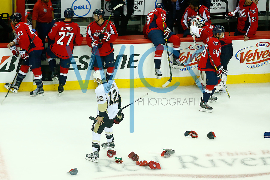 Ben Lovejoy #12 of the Pittsburgh Penguins skates through a sea of hats on the ice following the hat trick and game-winning overtime goal by T.J. Oshie #77 of the Washington Capitals during game one of the second round of the Stanley Cup Playoffs at Verizon Center in Washington D.C. on April 28, 2016. (Photo by Jared Wickerham / DKPS)