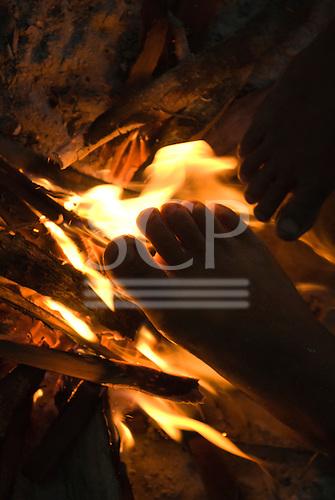 Ngoiwere Village, Mato Grosso State, Brazil. Kisedje (Suya),  warming feet by the fire.