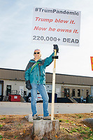"""A critic of US President Donald Trump's response to the ongoing Coronavirus (COVID-19) global pandemic holds a sign near people waiting in line to enter a Make America Great Again Victory Rally with US President Donald Trump in the final week before the Nov. 3 election at Pro Star Aviation in Londonderry, New Hampshire, on Sun., Oct. 25, 2020. Trump supporters surrounded the man with their signs and flags and many in the line jeered at him. His sign reads """"#TrumPandemic / Trump blew it. Now he owns it. / 220,000+ dead."""""""