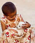 A girl tenderly cradles a puppy, Mandalay, Myanmar.