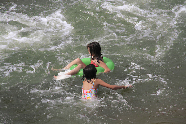 Two girls playing in an inner tube in whitewater, Denver, Colorado, USA.