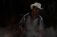 A Colombian farmer Ramiro Burbano controls the processing of panela in a rural sugar cane mill (trapiche) in San Agustín, Colombia, 18 April 2004. Panela, a solid block of raw, unrefined sugar, is made by cooking and evaporation of the sugar cane juice into a golden, sticky syrup which is then poured into the wooden molds and allowed to solidify. Having the taste like a cross between molasses and brown sugar, panela is served as a hot or cold infusion (aguapanela). Due to the large amounts of proteins, vitamins and minerals and thus, panela is believed to have healing powers. Cheaper than sugar, it is consumed by the majority of Colombians and it is a major source of calories for children from families with low socioeconomic status. With more than 70,000 farms that cultivate sugarcane for mills, panela production is an important economic activity in the Colombian countryside, employing around 350,000 people and being the second largest source of jobs after agricultural coffee production.