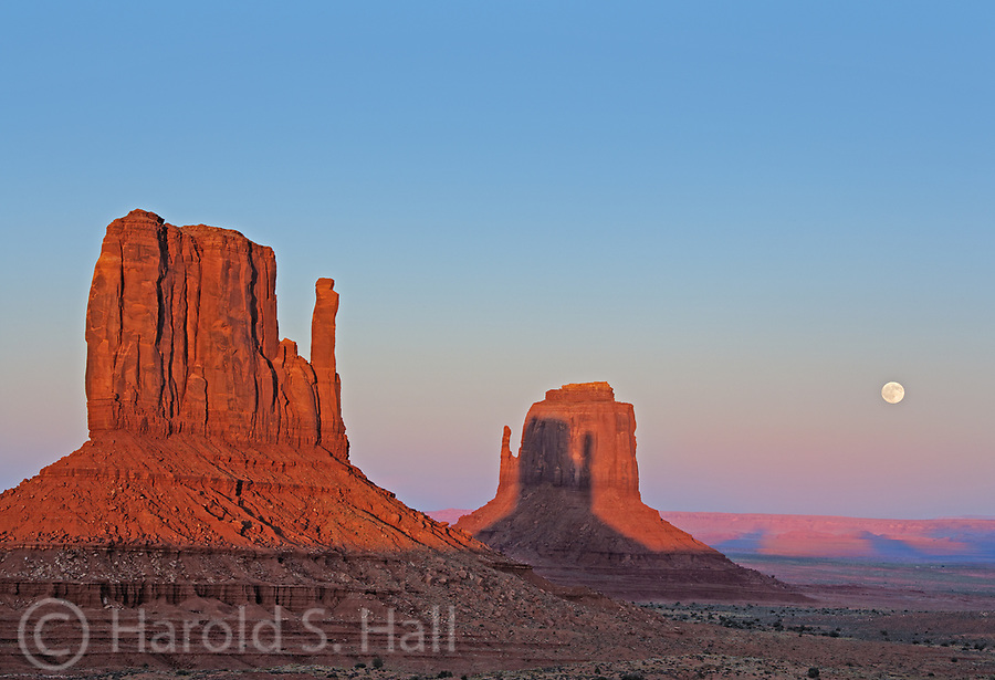 Twice a year, the shadow of the East Mitten is cast on the West Mitten by the setting sun in Monument Valley.  In addition the moon rises in the background.  Monument Valley lies on the boarder of Utah and Arizona, near the four corners region. It was made famous by film director John Ford in his western movies. These sandstone buttes are over 1,000 feet tall.