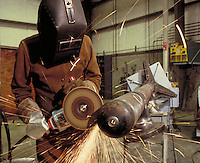 A worker grinds metal to specification. Grinder. machine, saw. occupations, machinery, equipment, trade. California.