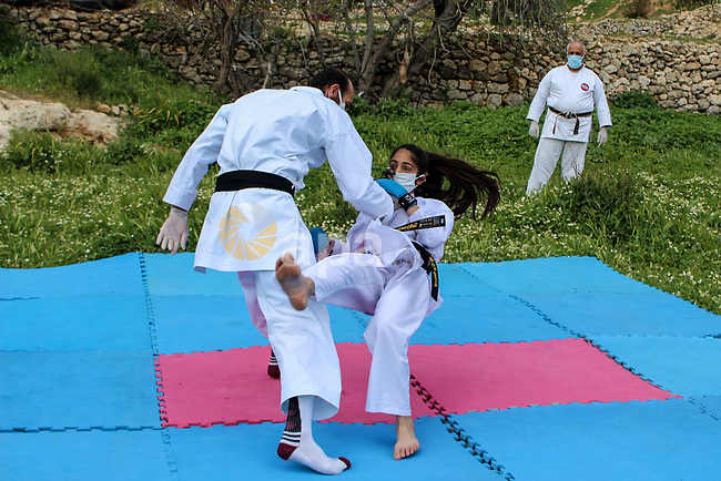 Palestinian national heroine Beesan al-Jubeh - under10-, trains with her family members, all wearing face masks and gloves due to the COVID-19 coronavirus pandemic, outside their house in the West Bank City of Hebron on April 9, 2020. Photo by Mosab Shawer