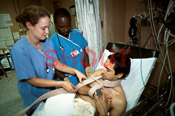 Doctor and nurse in an accident and emergency unit attending to a patient with a dislocated shoulder.
