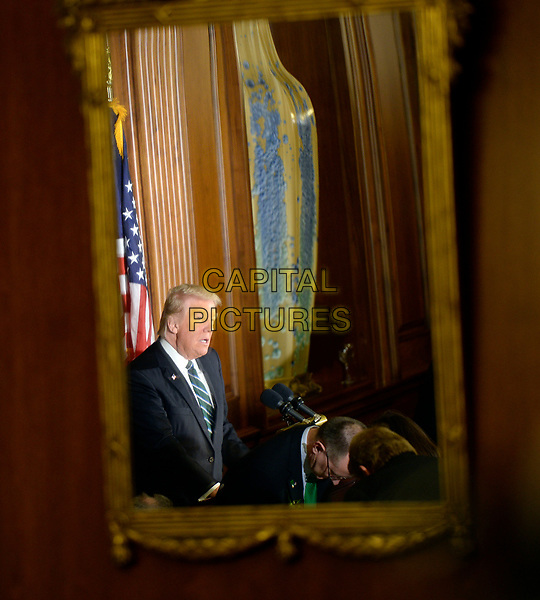 United States President Donald J. Trump is seen in a mirror as he speaks during the Friends of Ireland Luncheon at the U.S Capitol on March 16, 2017 in Washington, DC. <br /> CAP/MPI/CNP/RS<br /> ©RS/CNP/MPI/Capital Pictures