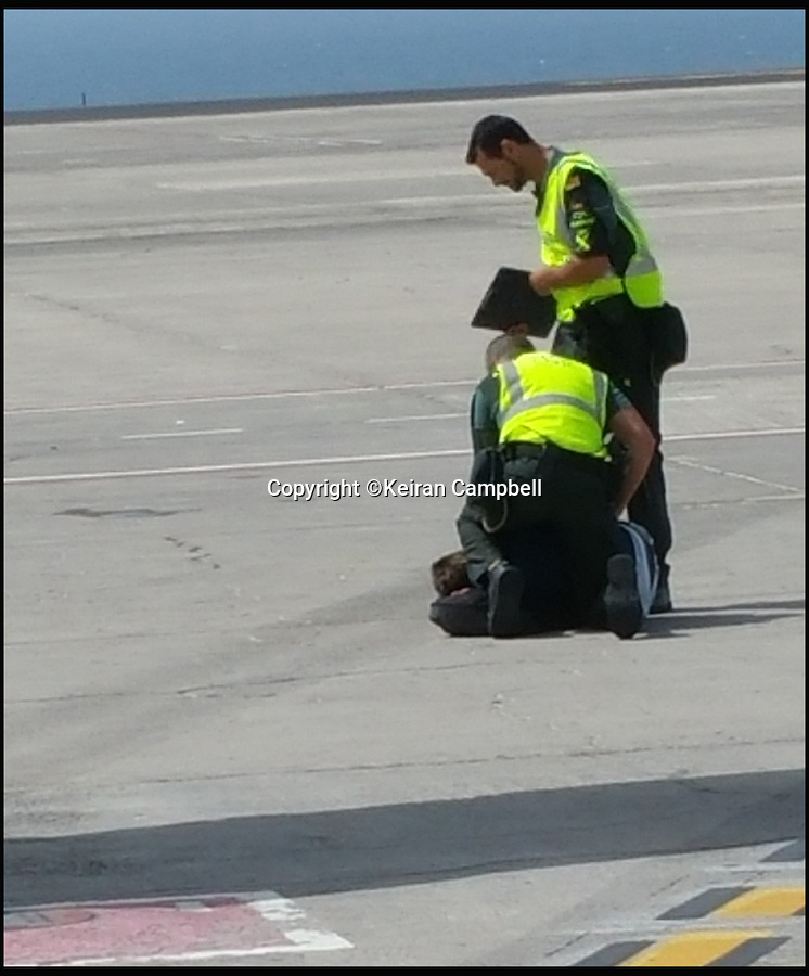 BNPS.co.uk (01202 558833)<br /> Pic: KeiranCampbell/BNPS<br /> <br /> This is the dramatic moment a British holidaymaker was pinned down by police on an airport apron after causing havoc among passengers on board a flight.<br /> <br /> Spanish police were waiting to detain the aggressive holidaymaker as the Ryanair plane landed in Tenerife after he was said to have acted inappropriately towards women passengers on board.<br /> <br /> The incident happened on a 7am flight from Bournemouth to Tenerife on Tuesday.