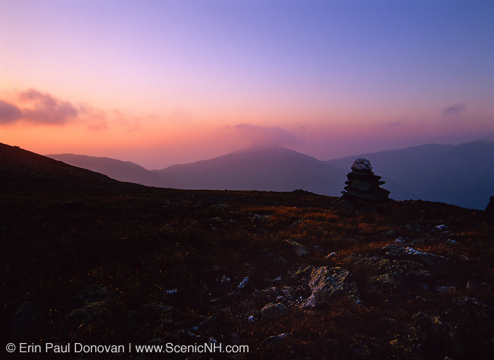 The silhouette of a rock cairn along the Alpine Garden Trail in Thompson and Meserve's Purchase in the New Hampshire White Mountains at sunset. The Northern Presidential Range is in the background.
