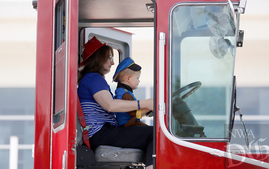 Joseph VerHoeven (cq), 2, sits with his mother Marissa Tuesday, June 8, 2021, in the tiller cab of the Fayetteville Fire Department Ladder 6 tractor drawn aerial as outside of Cross Church Fayetteville after his parents participated in the Boots and Badges Blood Donor Drive. The drive, hosted by the Community Blood Center of the Ozarks is a friendly competition between the Fire Department and the Police Department. Check out nwaonline.com/210609Daily/ and nwadg.com/photos for a photo gallery.<br /> (NWA Democrat-Gazette/David Gottschalk)