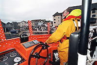 Royal National Lifeboat Institution crew aboard this Severn class, all weather type lifeboat preparing to go out on a rescue. The coxswain is at the helm piloting the boat he is navigating it away from the harbour and out to sea. This image may only be used to portray the subject in a positive manner..©shoutpictures.com..john@shoutpictures.com