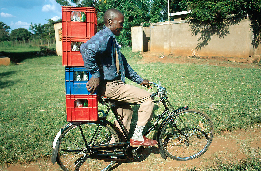 Uganda. Kayunga district. Kayunga. A man, wearing a tie and suspenders, rides a bicycle while carrying a pile of emtpy bottles of soft drinks. © 2004 Didier Ruef