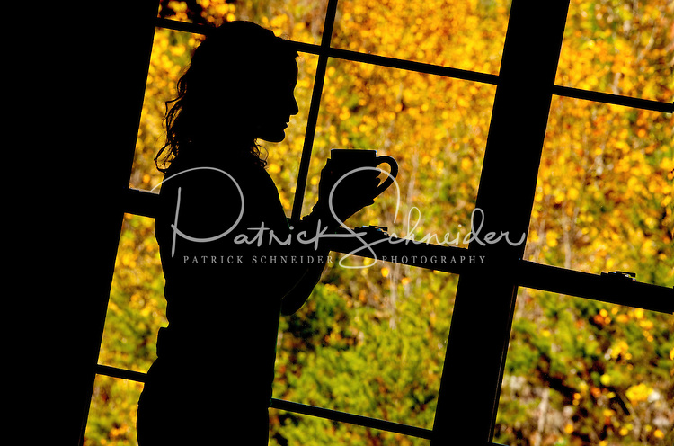 Silhouette of a woman holding a coffee cup with a canopy of autumn leaves outside a window behind her. Photo taken in Asheville NC's Biltmore Park Town Square, a planned community of residential living, office spaces and shopping.