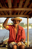 Para State, Amazon, Brazil. 'Captain Joao', a fisherman on the river at Conceicao do Araguaia, aboard his boat smoking.