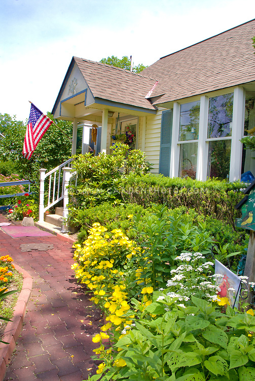 Curb appeal house front entry entrance walkway path, American flag patriotic, Oenothera blue skies sunny day