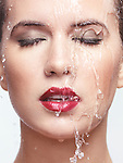Closeup of a young beautiful woman face with red lipstick and makeup with water running over it Image © MaximImages, License at https://www.maximimages.com