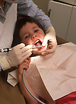 Young girl gets her teeth cleaned at dentists office