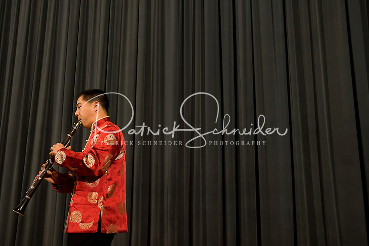 A man plays the clarinet while dressed in colorful Chinese attire Chinese New Year Celebration at UNC Charlotte in Charlotte, NC.