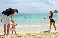 A mother and father encouraging their young daughter to walk on the shore of Lanikai Beach, O'ahu.