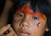 Xingu Indigenous Park, Mato Grosso State, Brazil. Aldeia Morena (Kamaiura). Girl having her face painted with black genipapu and red urucum.